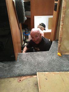 On voit ici un Propriétaire qui fait l'installations de tapis dans un bateau motorise roulotte qui sourit car il est très heureux du travail de ce poseur de tapis.